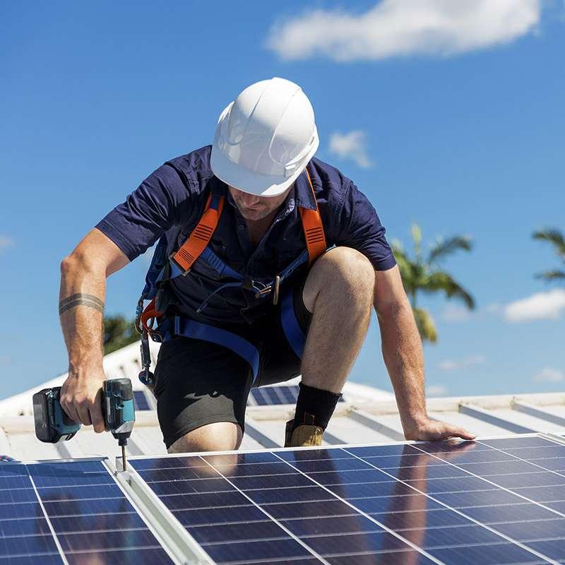 Man on roof installing solar panel